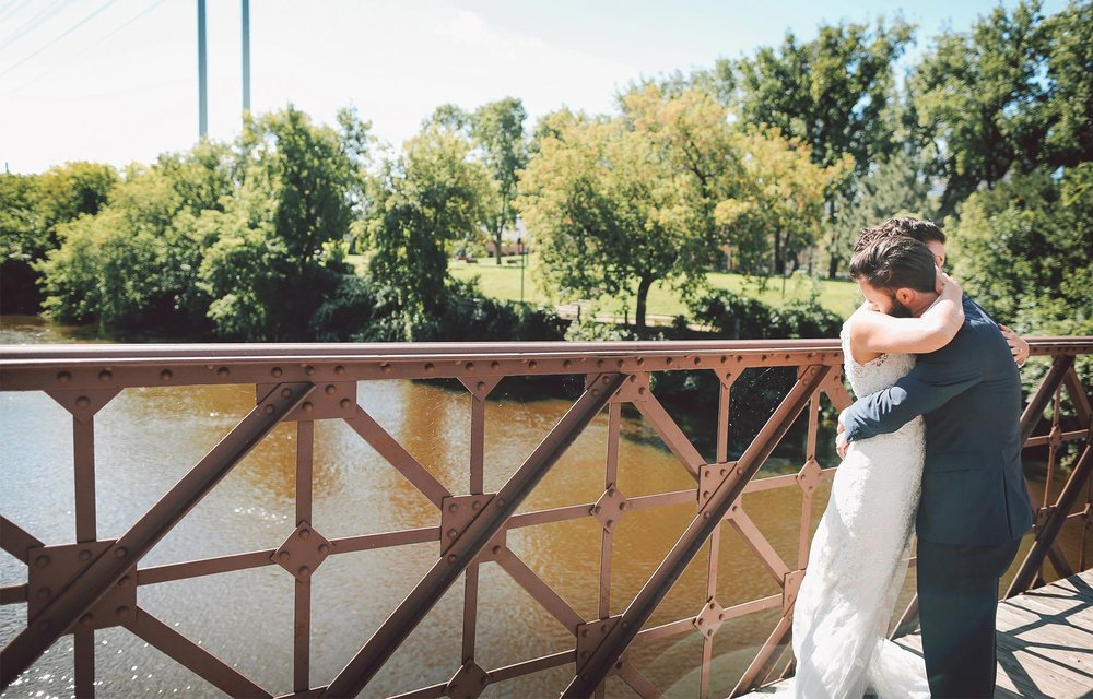 07-Minneapolis-Minnesota-Wedding-Photographer-by-Andrew-Vick-Photography-Summer-First-Meeting-Look-Bride-Groom-Merriam-Street-Bridge-Mississippi-River-Embrace-Hug-Vintage-Ashley-and-Eric.jpg