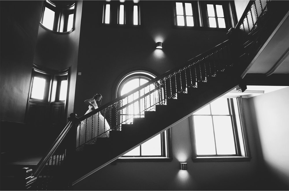 05-Saint-Paul-Minnesota-Wedding-Photographer-by-Andrew-Vick-Photography-Winter-New-Years-Eve-Embassy-Suites-First-Meeting-Look-Bride-Staircase-Stairs-Black-and-White-Emily-and-Michael.jpg