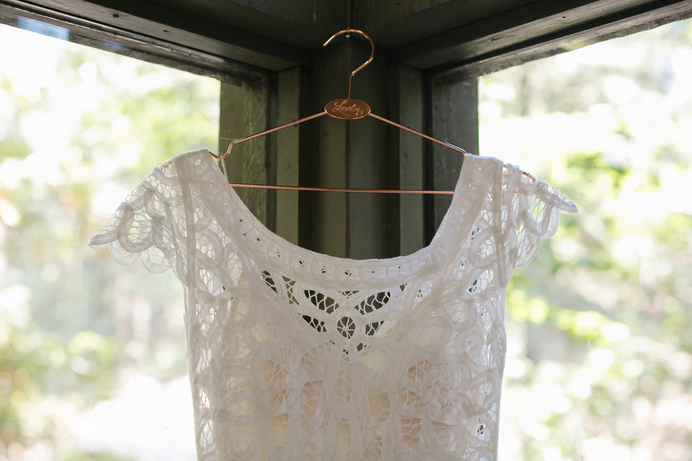 Lace wedding dress on copper hanger in front of windows