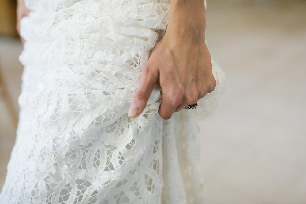 Bride holding her wedding dress as she walks