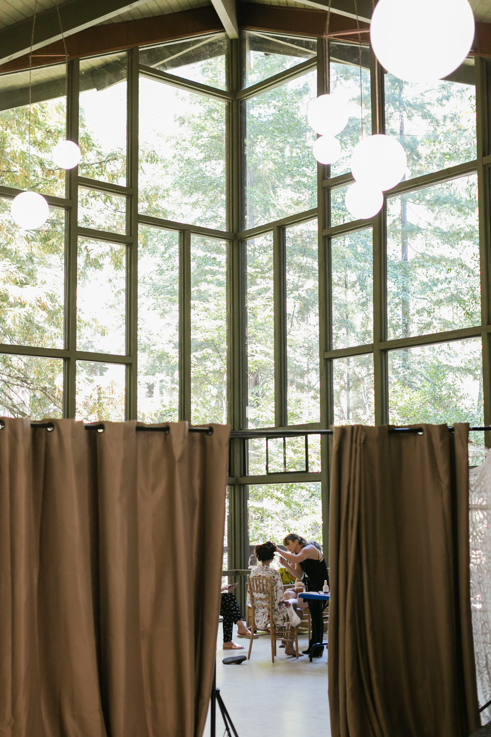 Bride gets her hair and makeup done in front of huge windows among the trees