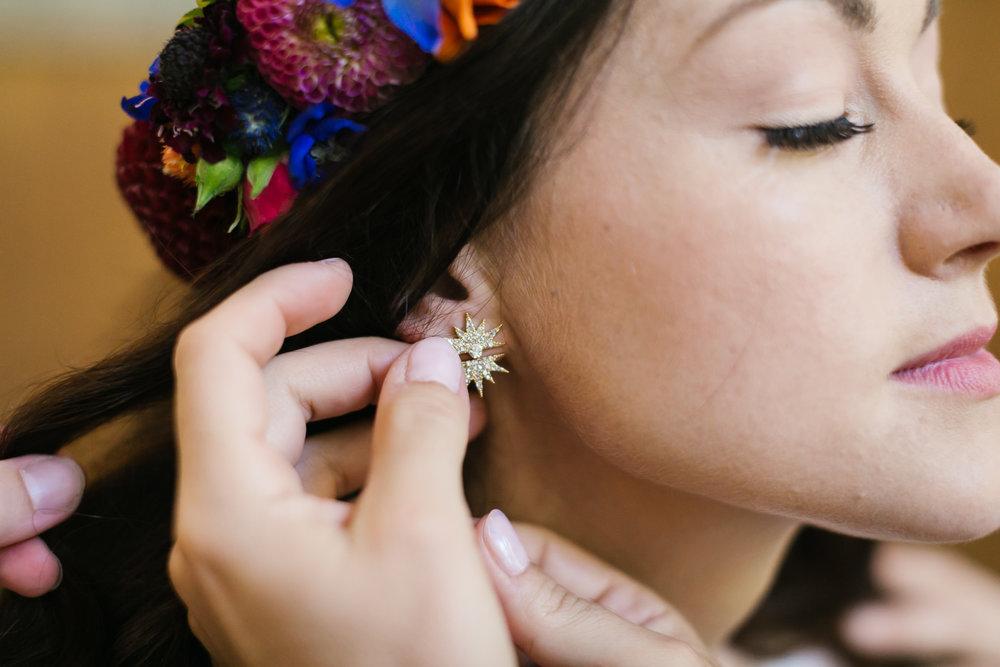Bride's starburst earrings being put on