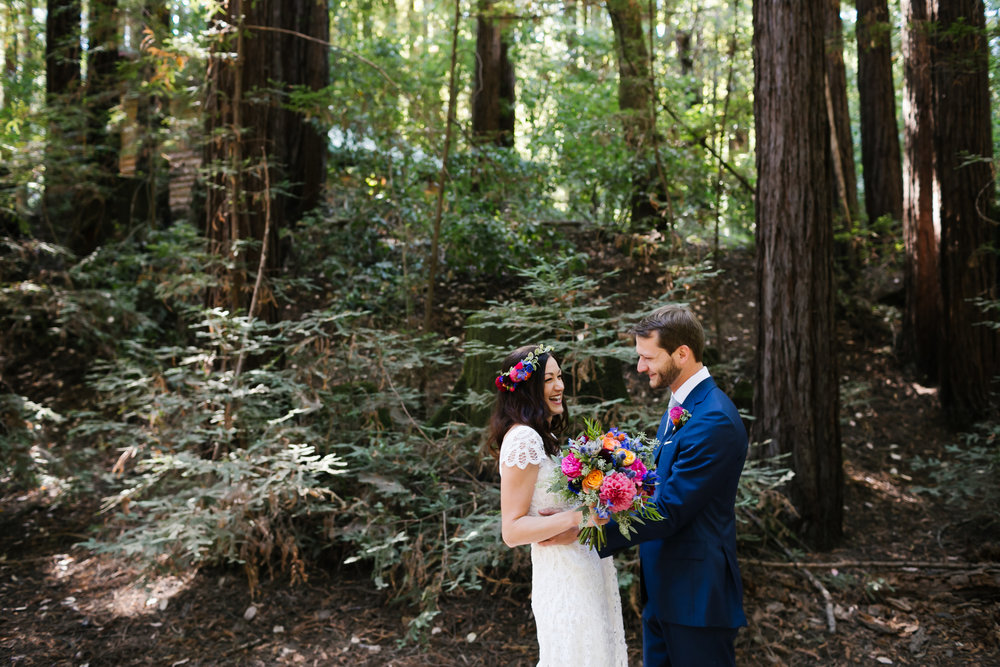 Colorful bride and groom laugh as they see each other for the first time