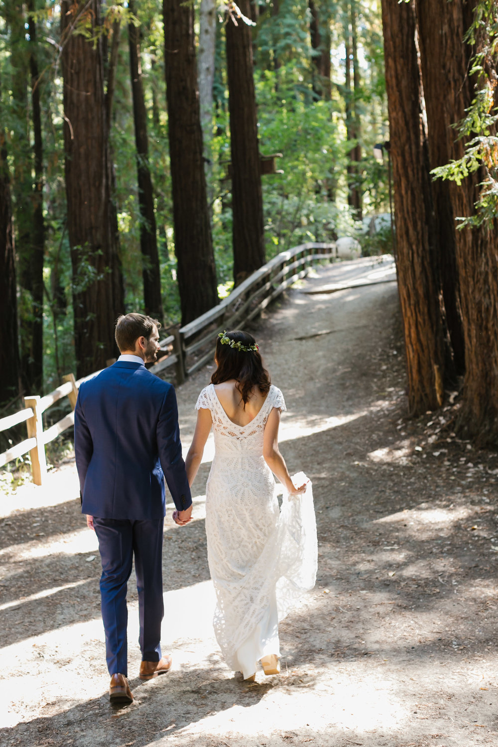 Bride holds her lace wedding dress and holds hands with her husband as they walk into the forest
