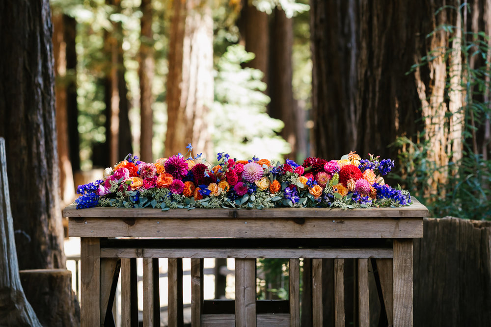 Outdoor ceremony altar covered in colorful flowers in redwood forest