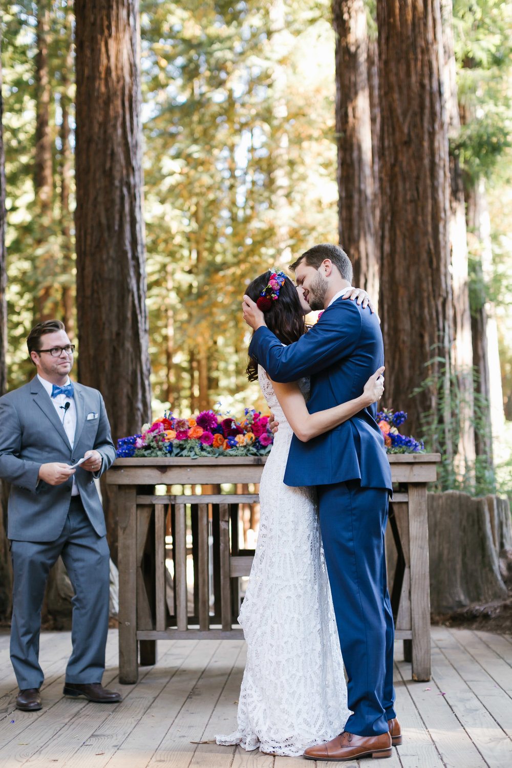 Colorful couple share their first kiss during their wedding ceremony at outdoor chapel under the trees