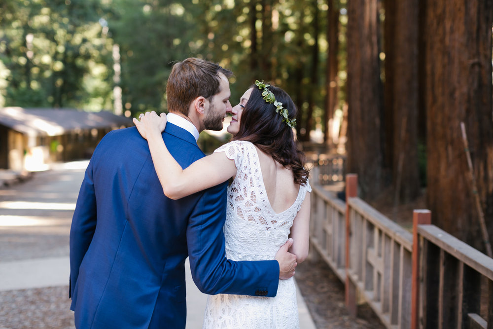 Groom in blue suit is about to kiss his bride in white lace gown