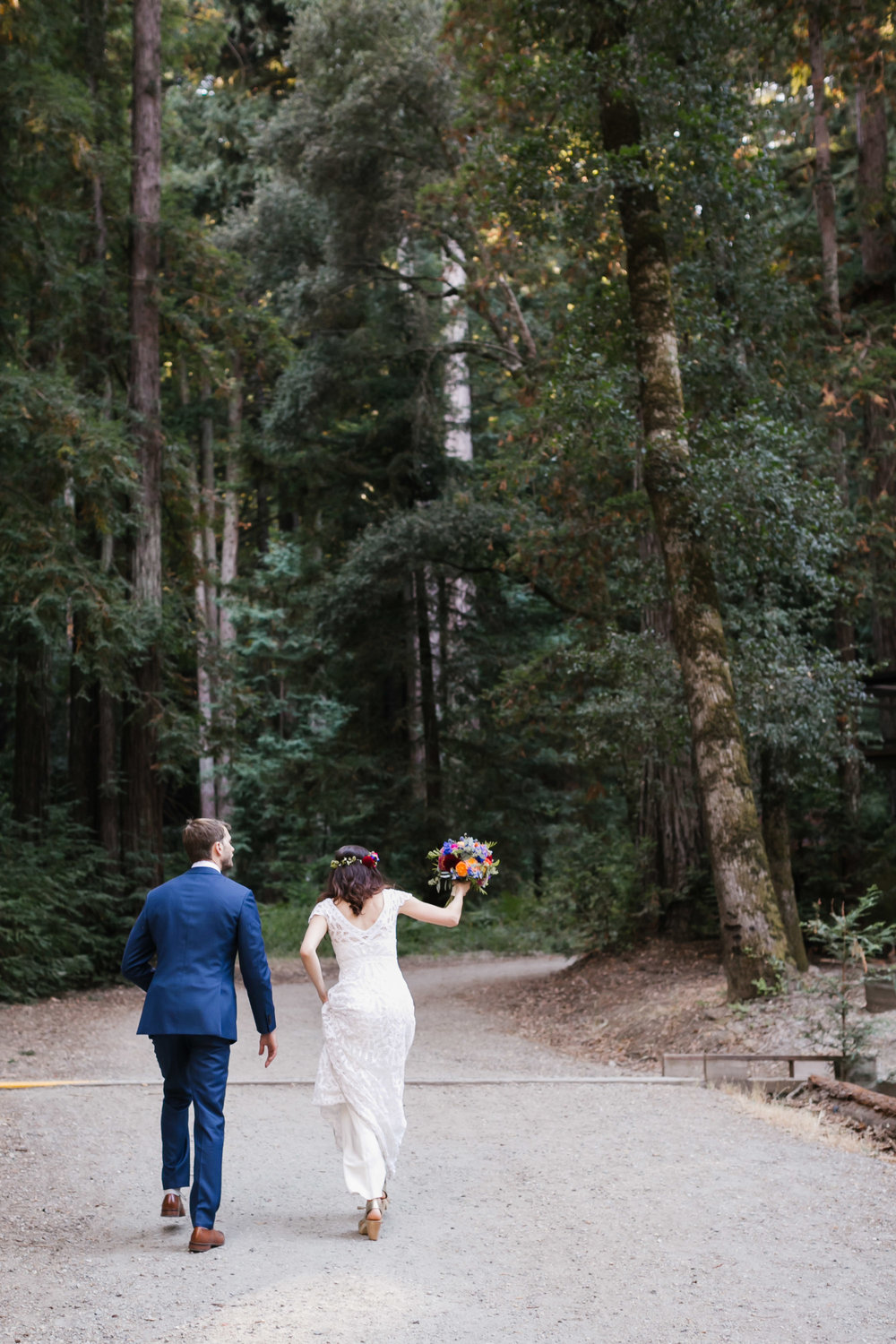 Wedding couple walk up a path together