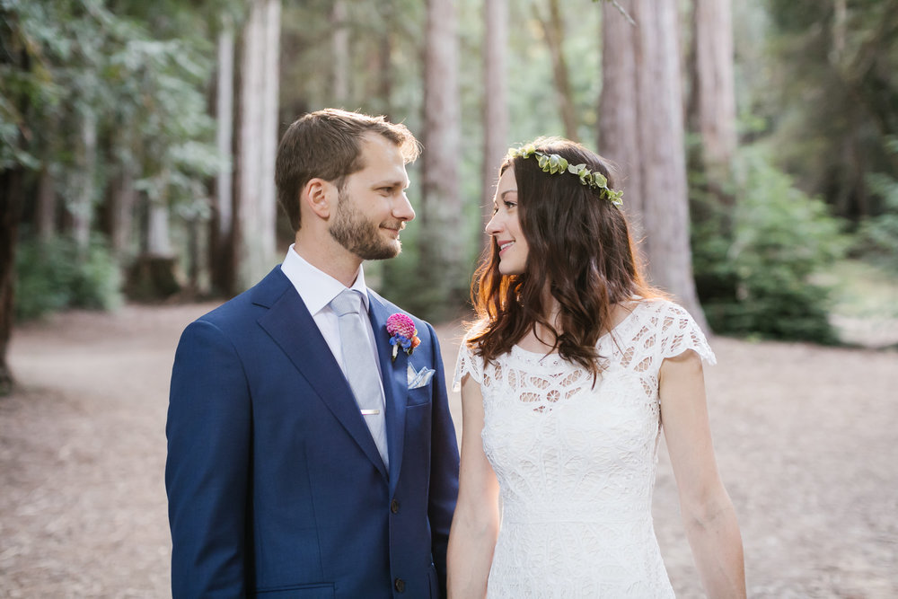 Wedding couple share a look with the sun streaming through the trees