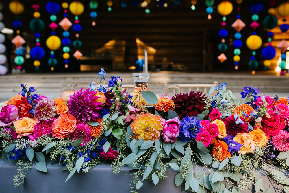 Sweetheart table is covered in large colorful flowers