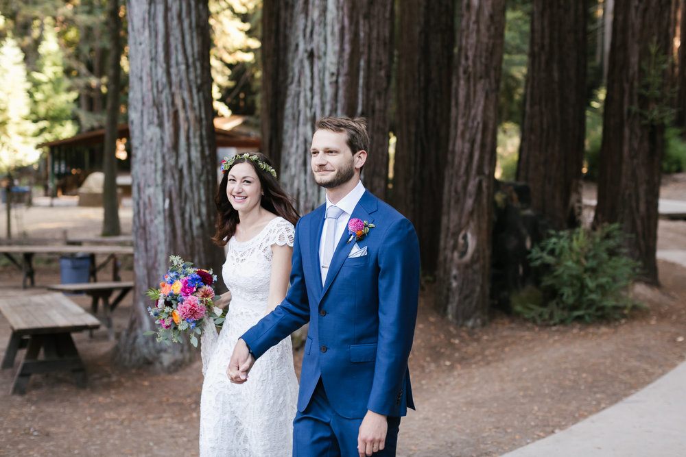 Bright wedding couple happily walk into their reception