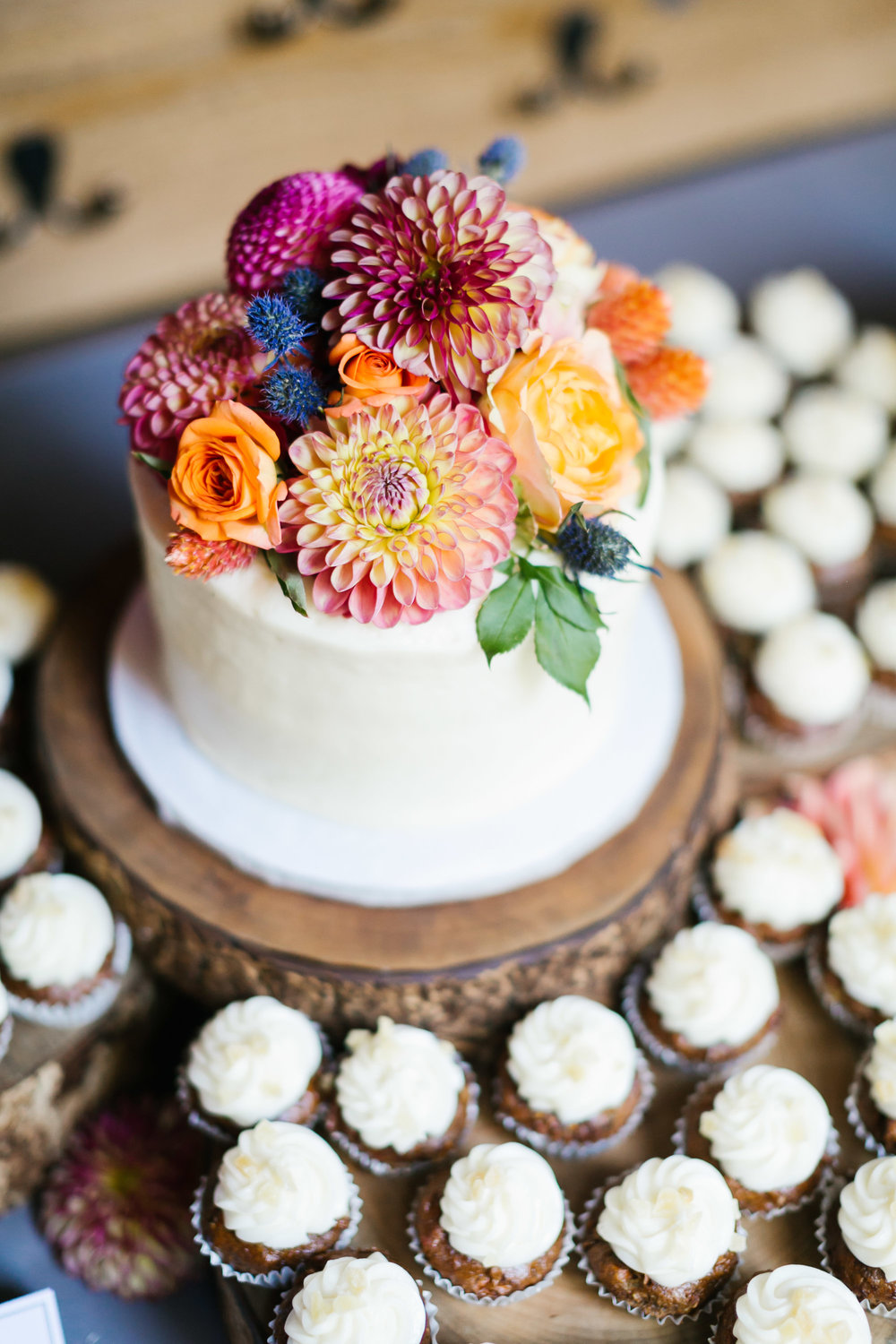 Small wedding cake topped with colorful dahlias and surrounded by cupcakes