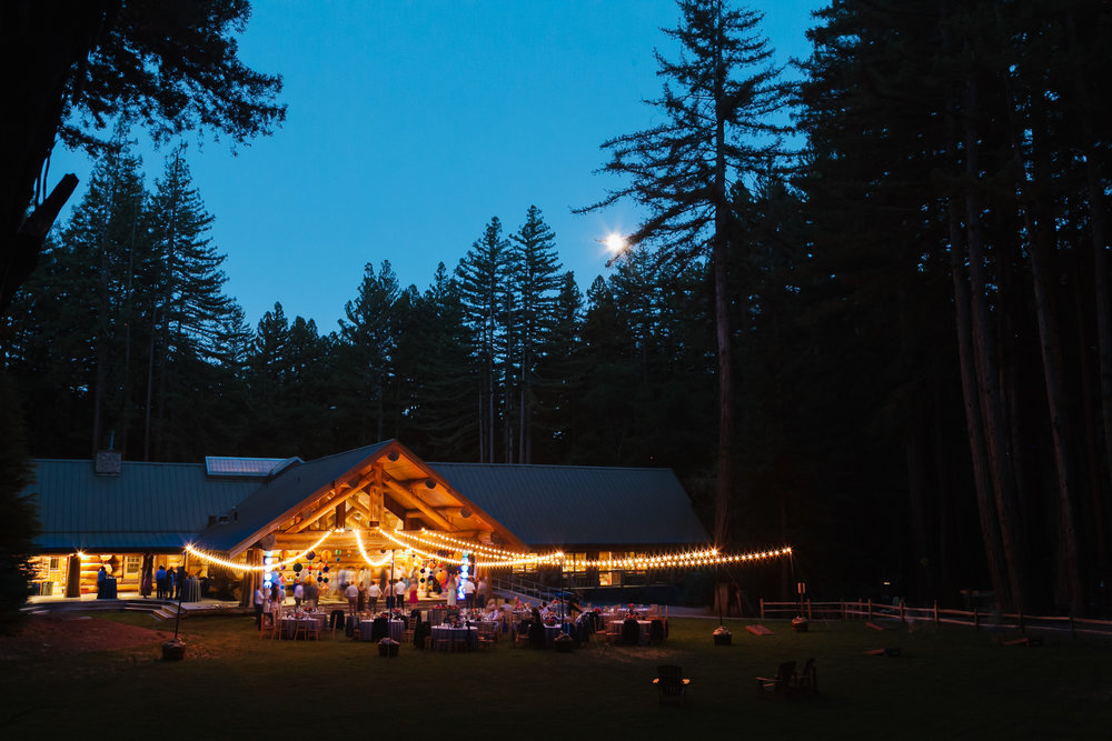 Full moon peaks above tree line behind glowing wood lodge with market lights decorating the lawn