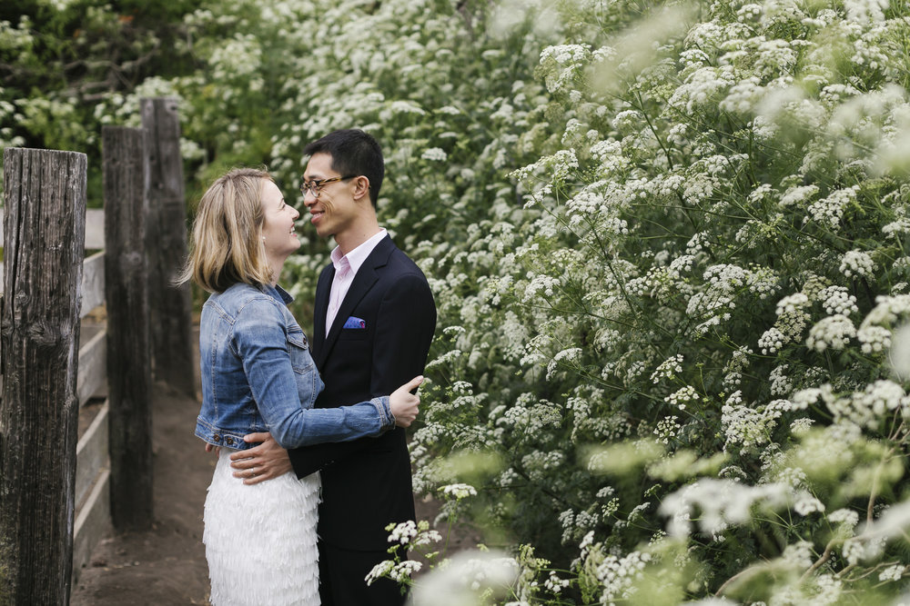 Couple hugging next to blooming flowers and goats at Slide Ranch
