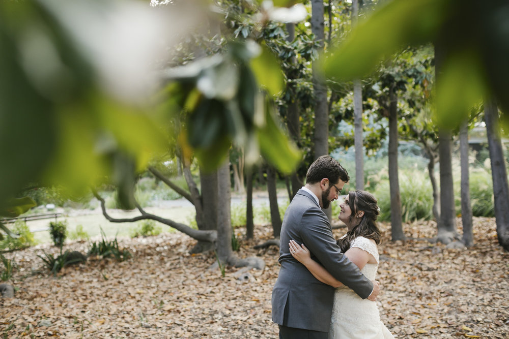 A wedding couple hug surrounded by trees at the Marin Art and Garden Center