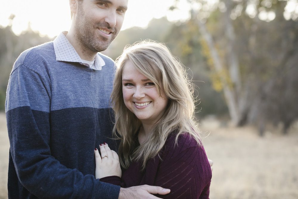 An engaged couple smile together at sunset at Arroyo Seco in Pasadena