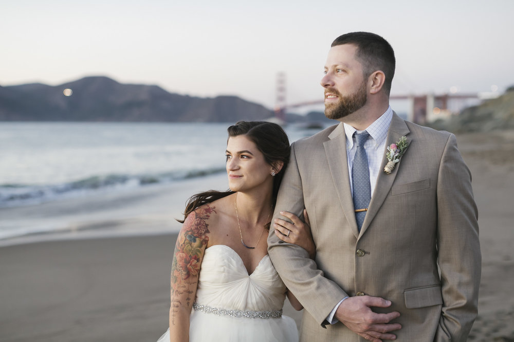 A wedding couple enjoy the sunset together in front of the Golden Gate Bridge on Baker Beach in San Francisco