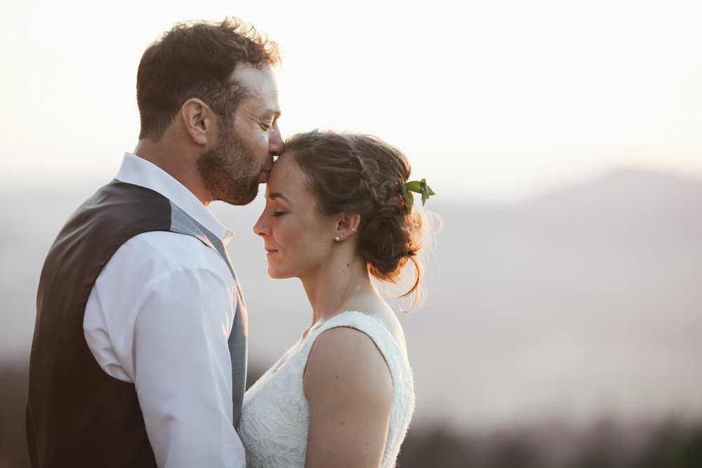 Husband kisses his wife's forehead at sunset on their wedding day