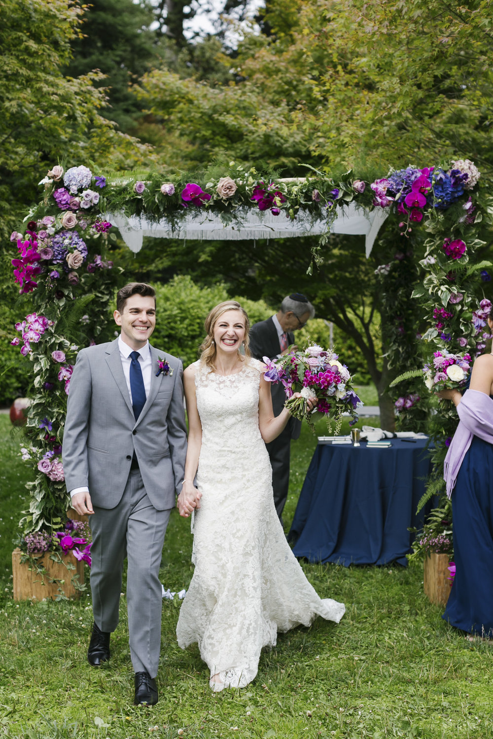Just married couple leaving their ceremony with beautiful floral in the background