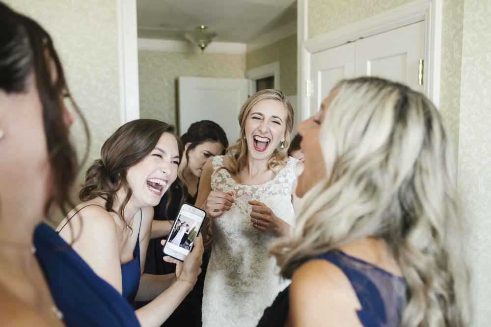 Bride laughs after seeing photo on bridesmaid's phone