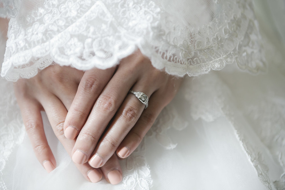 Detail shot of bride wearing her wedding ring surrounded by lace veil
