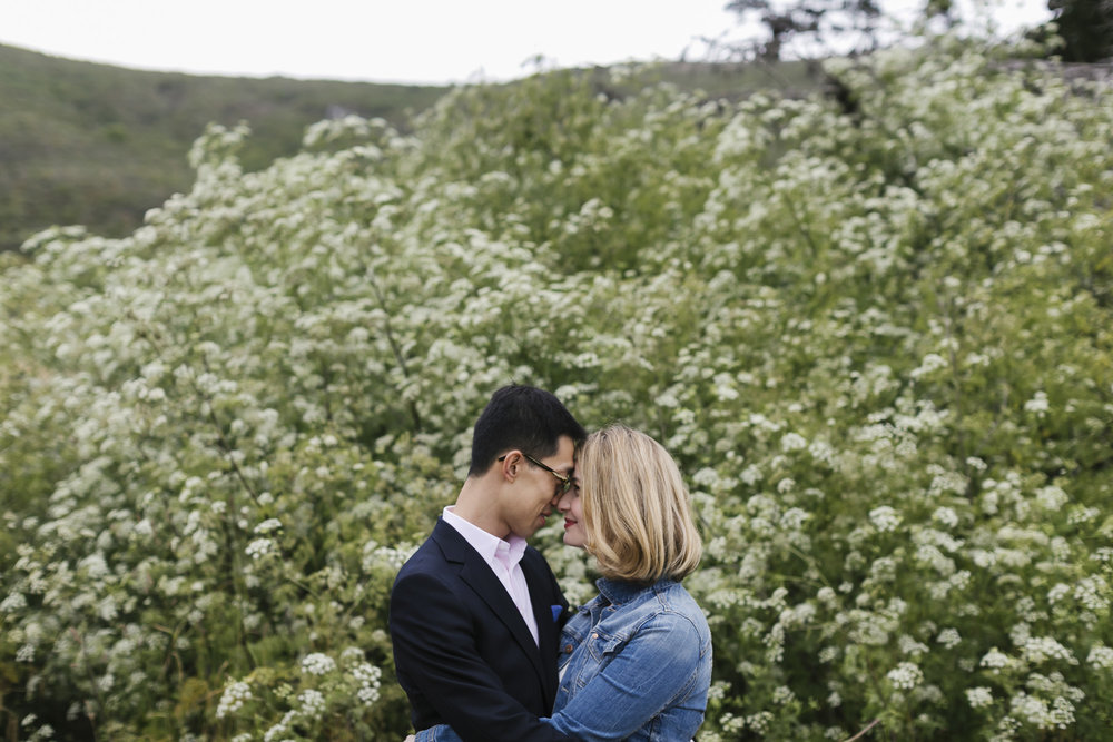 Engaged couple get close in front of white flowers blooming
