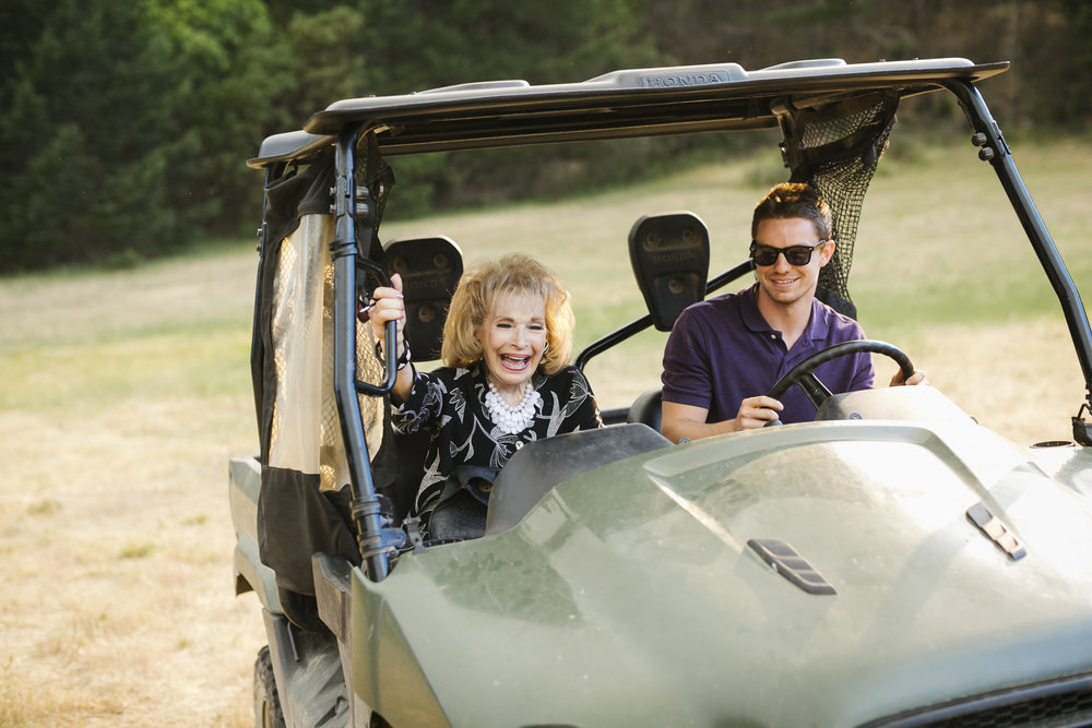 Grandmother laughs while riding shotgun in an ATV with her grandson driving