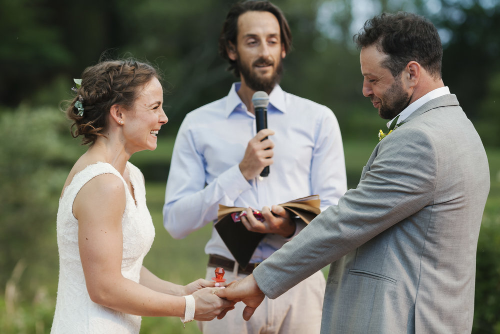Bride wearing a red ring pop laughs as her husband makes a funny face during their wedding ceremony