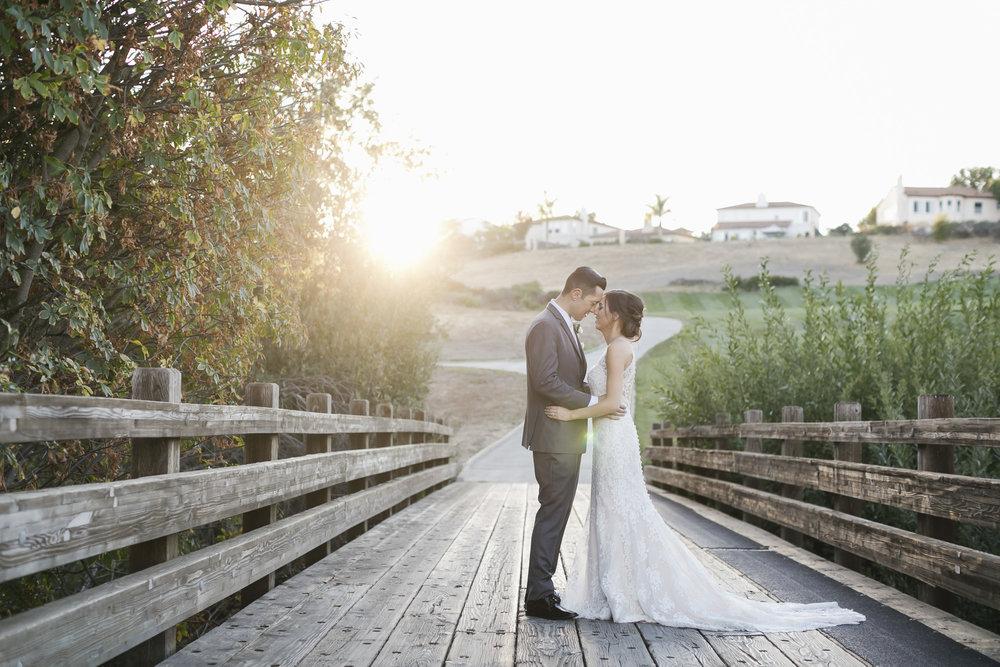 Wedding couple embrace on bridge with sun setting on the ridge behind them