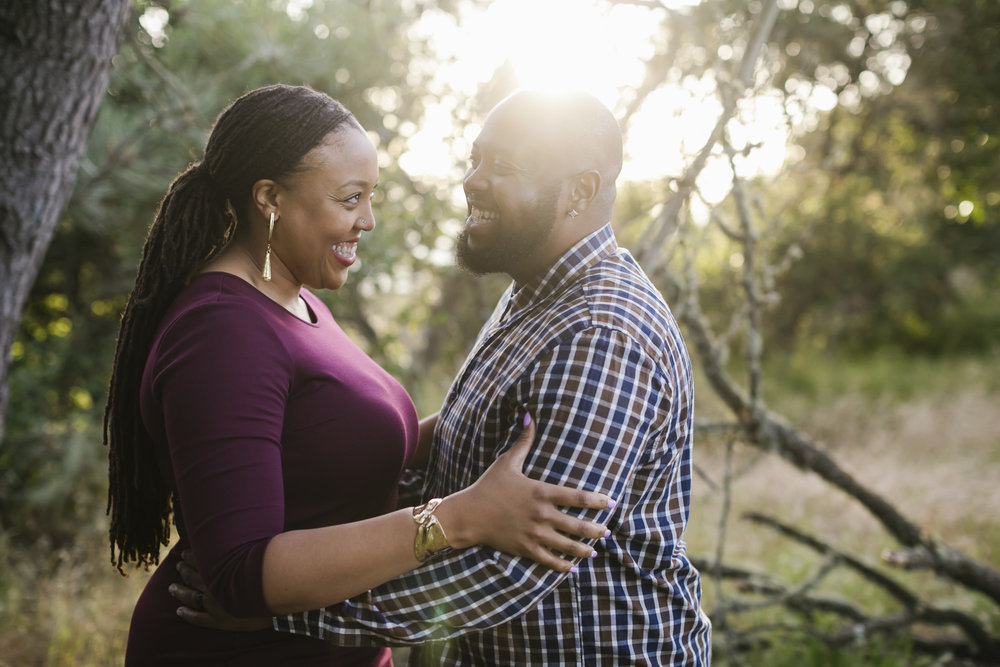 An engaged couple laughs together in the late afternoon sun