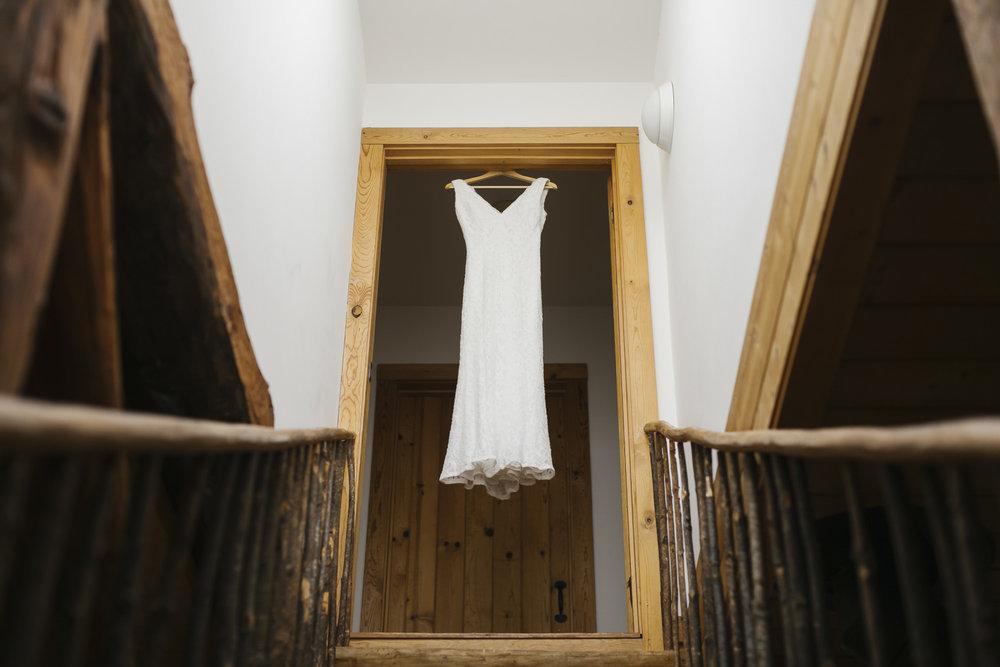 A bride's wedding dress hangs in the doorway of a wood cabin