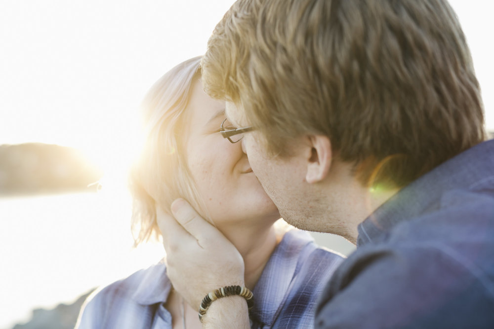 An engaged couple kiss at sunset by the water