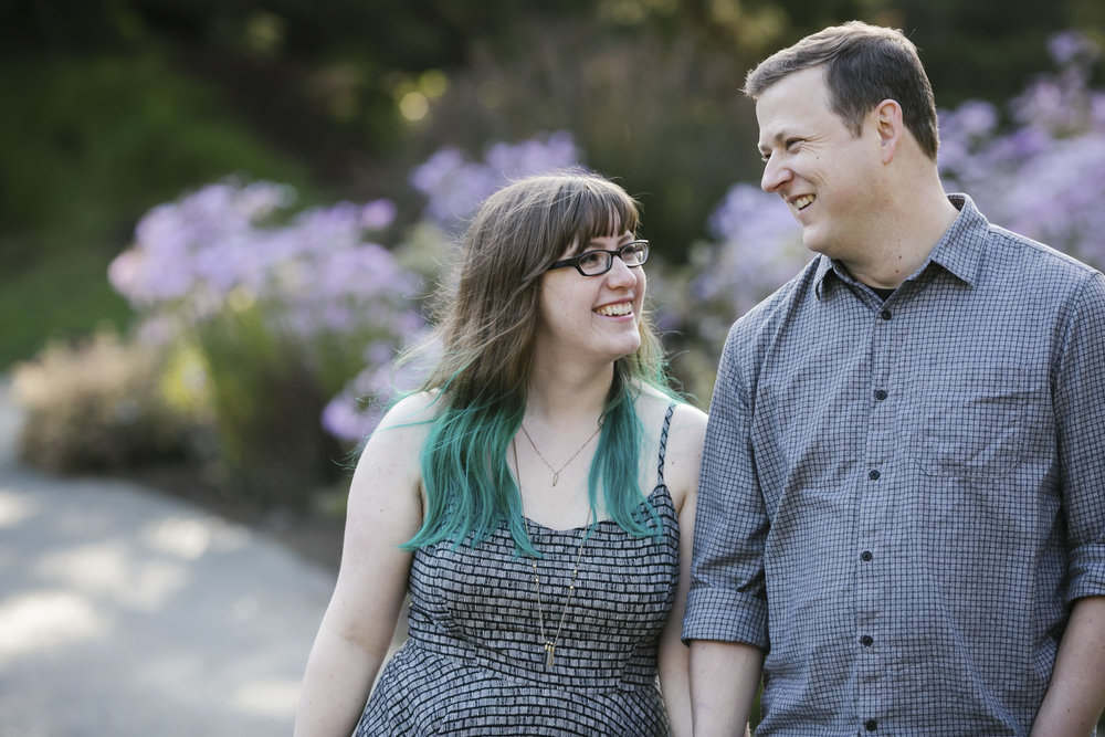 An engaged couple smile at each other in the San Francisco Botanical Gardens