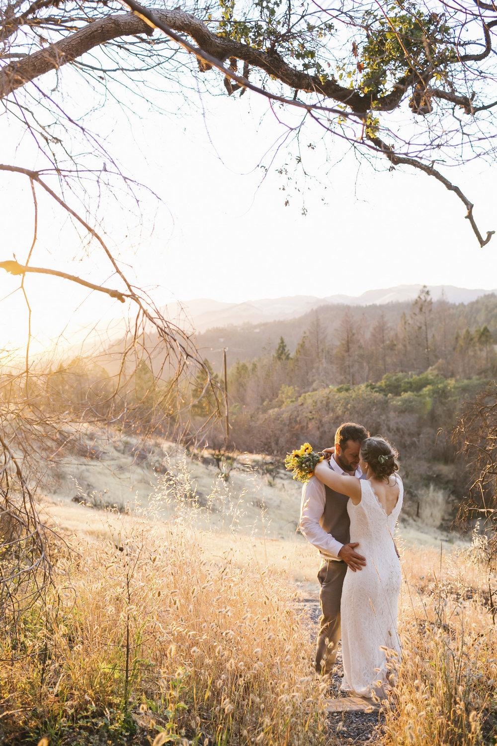 A wedding couple hug at sunset on a golden hillside