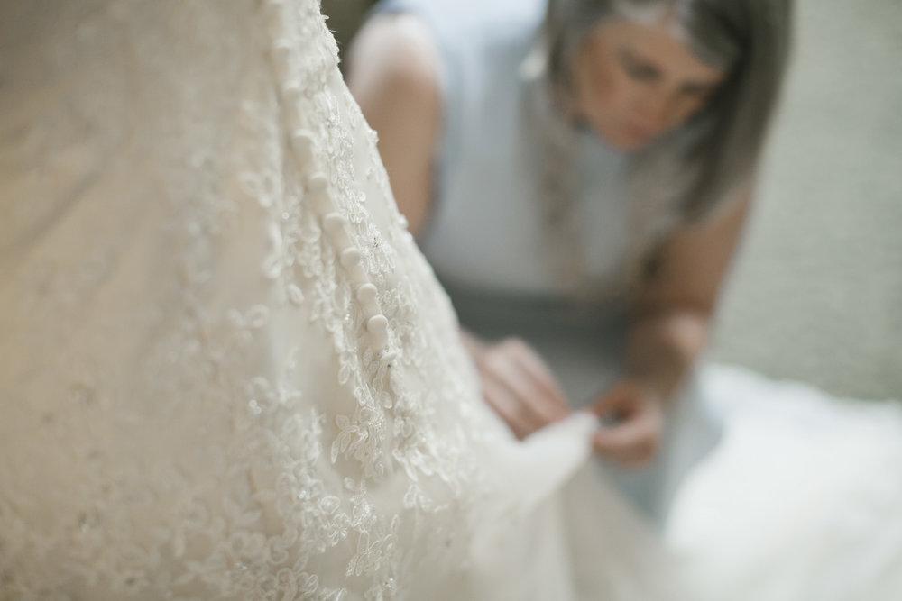 Bride's mother fixes her daughter's wedding dress