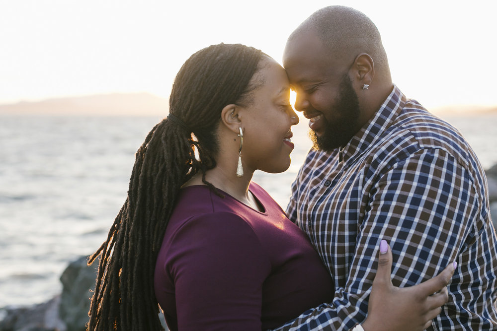 Engaged couple touches foreheads with the sun setting into the ocean behind them
