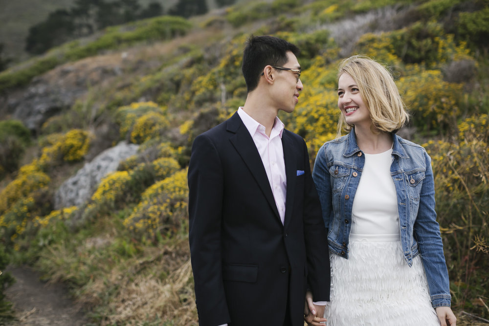 Engaged Couple share a loving look in front of yellow wildflowers