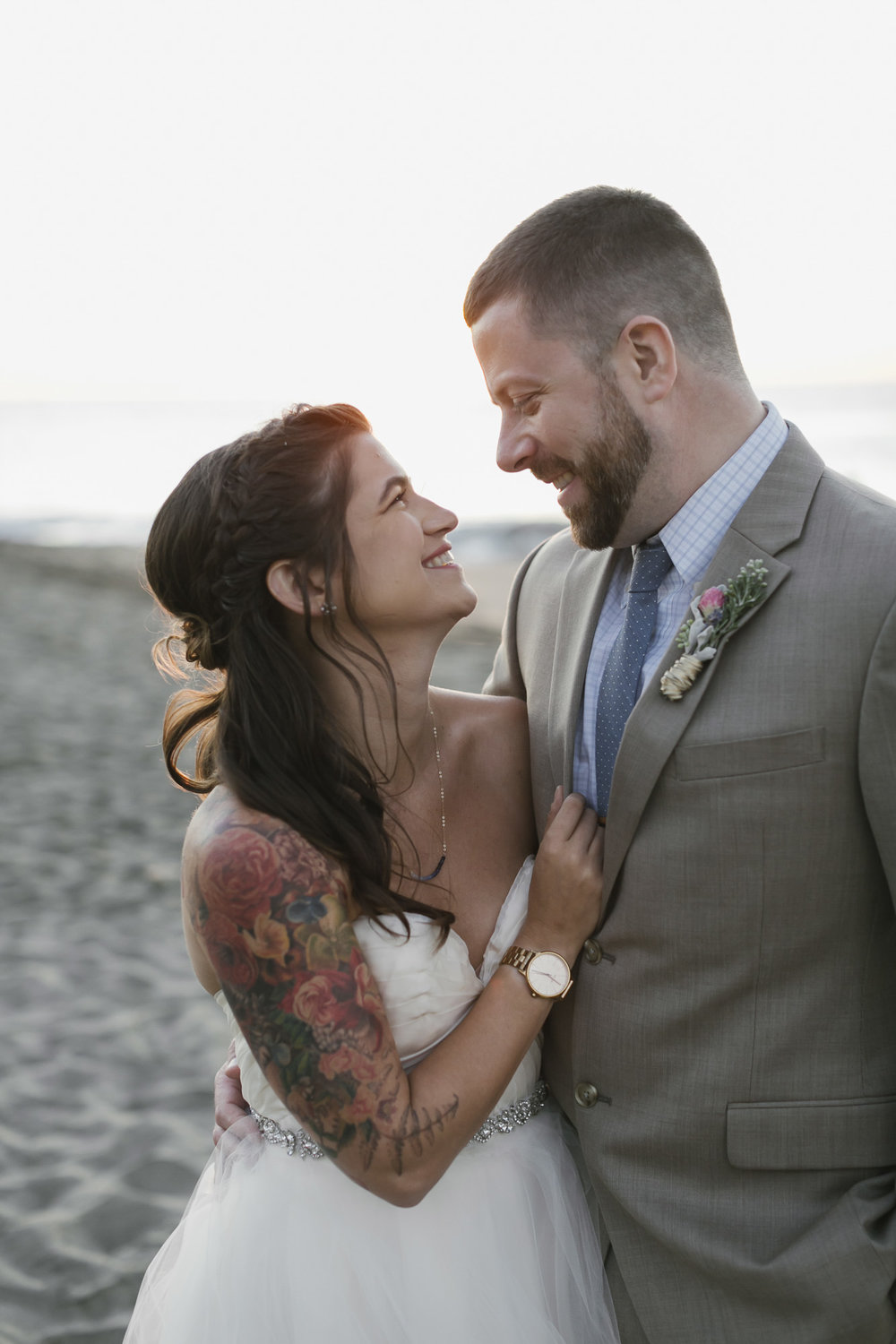 A tattooed bride wearing a man's watch laughs with her husband at Baker Beach at sunset