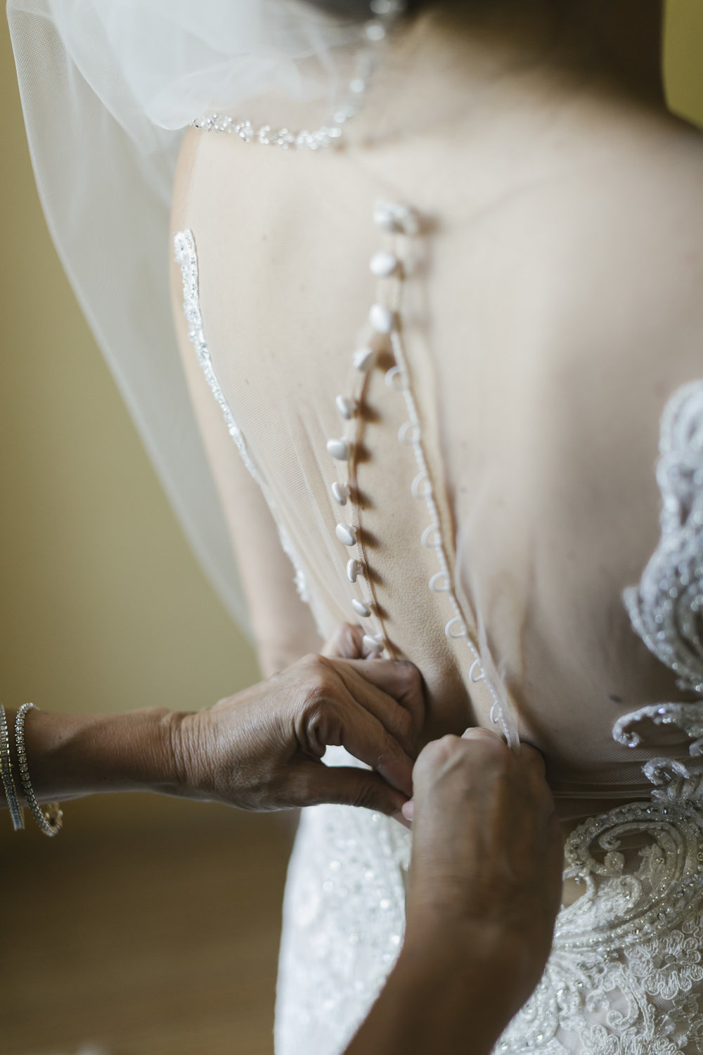 Mother of the bride buttoning her daughter's lace wedding dress