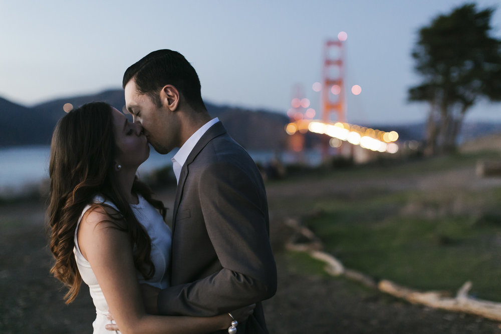 Engaged couple kiss at sunset in front of the Golden Gate bridge