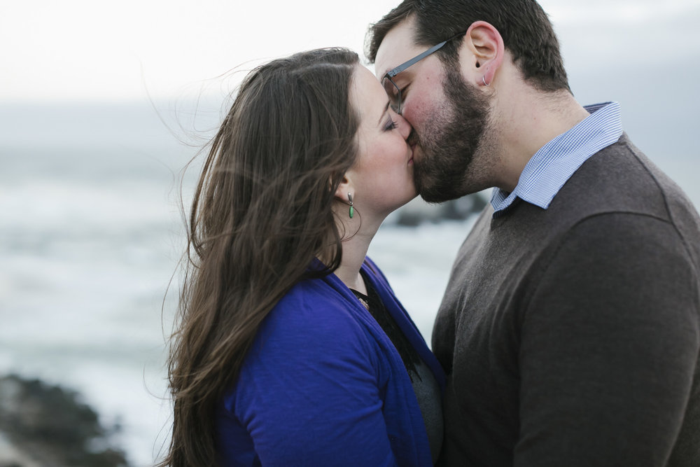 Engaged couple kiss at Lands End with ocean in the background