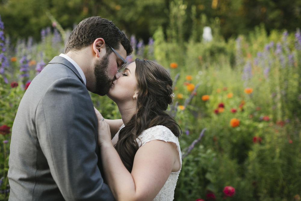 Wedding couple kiss in front of colorful flowers in Marin
