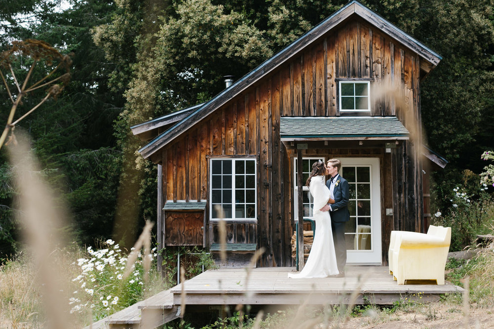 Wedding couple kiss in front of charming wood cabin