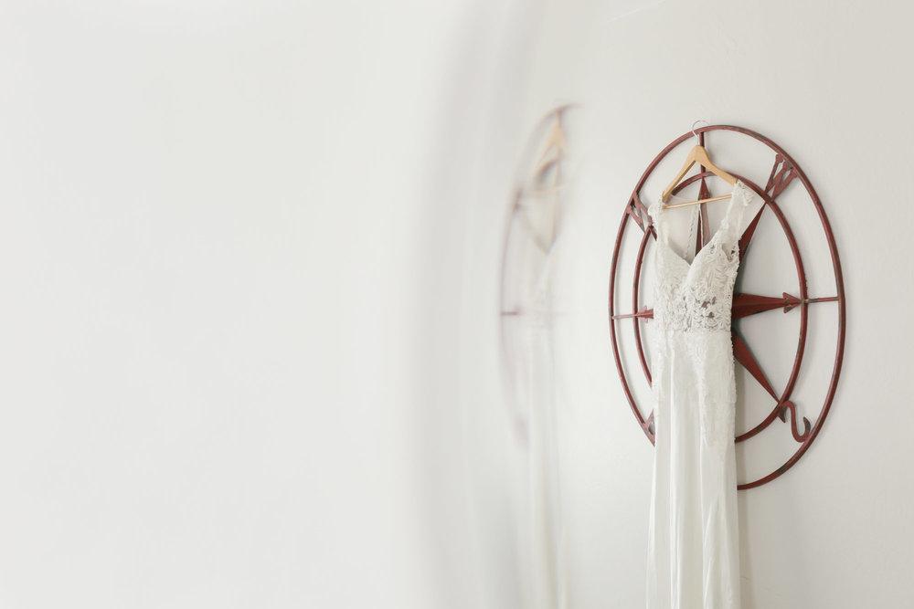 Custom lace wedding dress hangs on compass art
