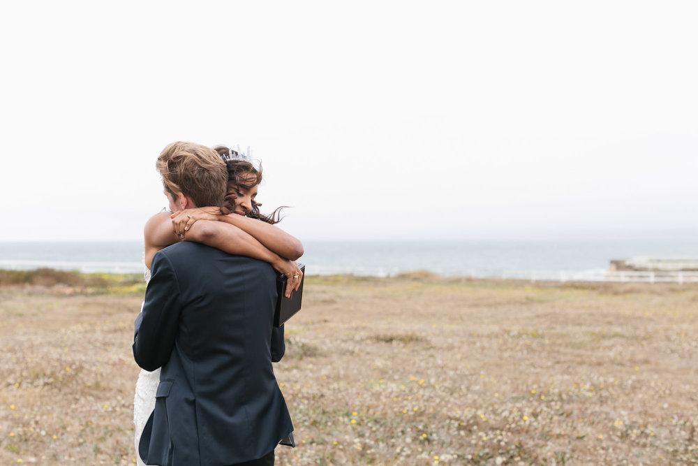Wedding couple hug in meadow along the windy coast of Northern California