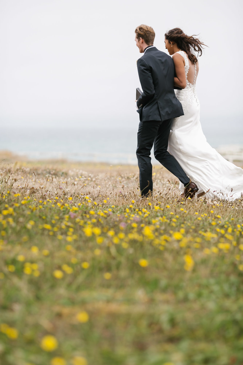 Wedding couple walk away together in field of wildflowers