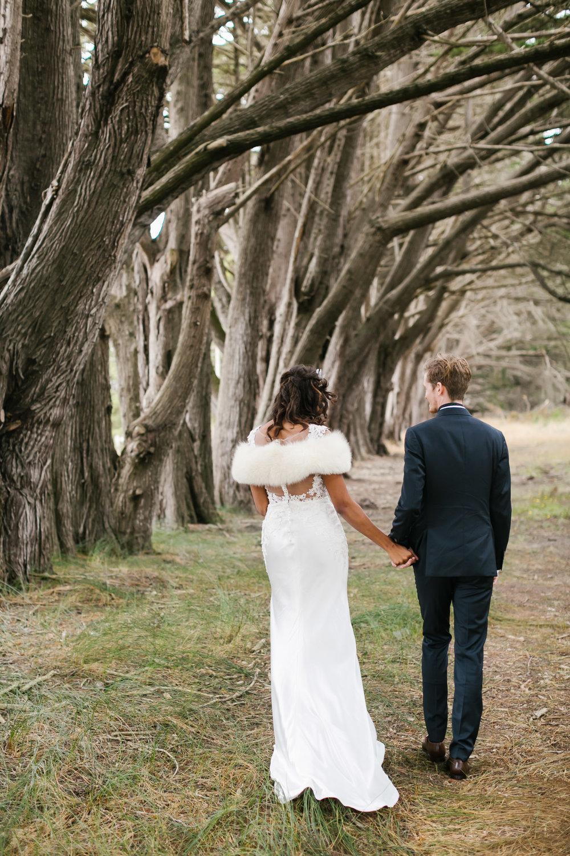 Bride wearing crystal crown walks with groom among coastal trees
