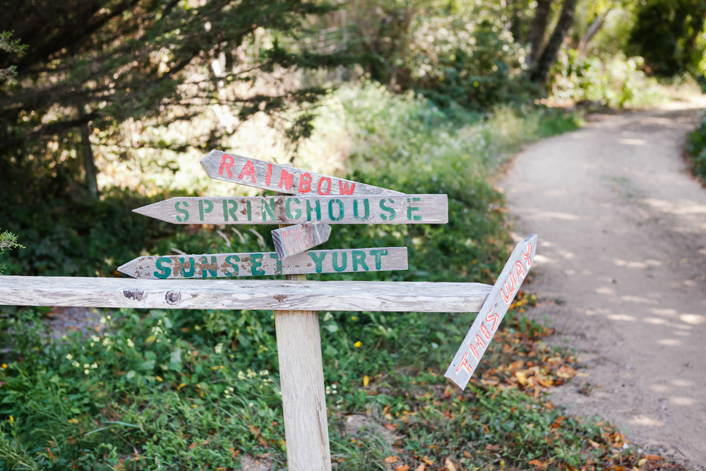 signs pointing to various cabins at oz farm in mendocino area