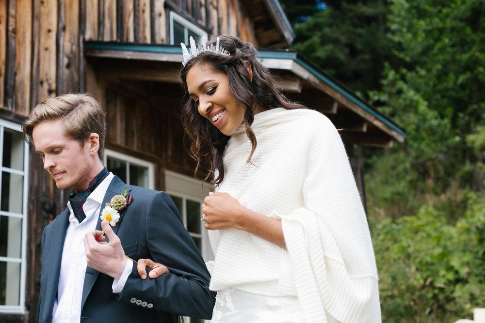 Bride wearing crystal crown walks with her groom in front of wood cabin