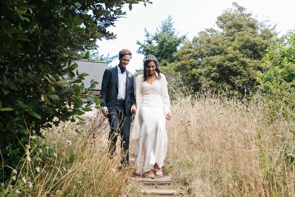 Bride wearing crystal crown and custom lace dress walks down steps with her groom